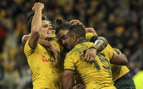 Australia's Kurtley Beale (R) celebrates with Lukhan Salakaia (C) and Matt Toomua (L) after beating the All Blacks in Perth