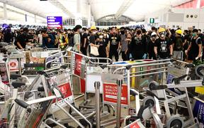 Pro-democracy protestors block the entrance to the airport terminals after a scuffle with police at Hong Kong's international airport on August 13, 2019