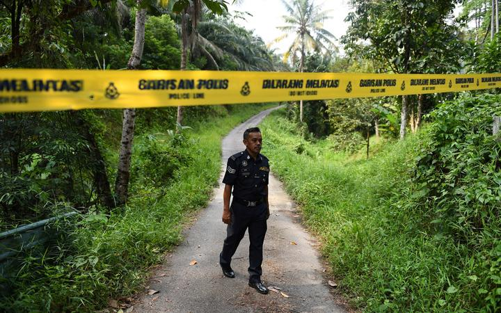 A policeman walks near a police line at an entrance to the Dusun Resort, where missing 15-year-old teenager Nora Quoirin was last seen, in Seremban on 13 August.