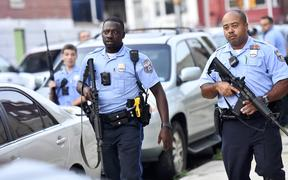 Police officers congregate outside a residence while responding to a shooting on August 14, 2019 in Philadelphia, Pennsylvania. At least six police officers were reportedly wounded in an hours-long standoff.