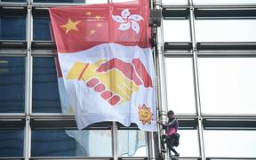 French urban climber Alain Robert, popularly known as the French Spiderman, secures a banner, showing shaking hands below a depiction of the Chinese and Hong Kong flags, during his ascent of the Cheung Kong Center building in Hong Kong on August 16, 2019.