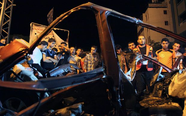 People gather around the wreckage of a car after it was hit by an Israeli strike in Gaza city.