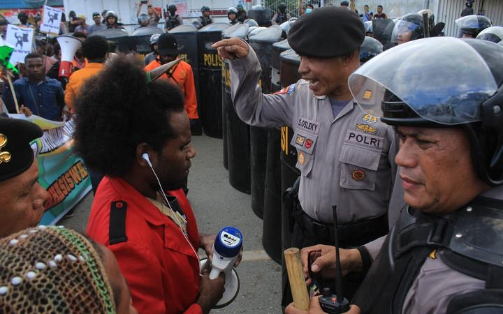 Indonesian police confront a protest leader.