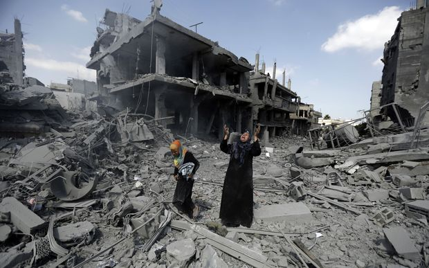 A Palestinian woman pauses amid destroyed buildings in the northern district of Beit Hanun in the Gaza Strip.