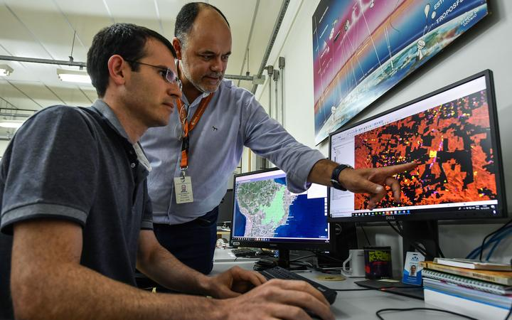 Brazilian coordinator of the Amazon Program, Claudio Almeida, speaks with a researcher at the National Institute for Space Research (INPE) headquarters, in Sao Jose dos Campos.
