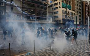 Riot police fire tear gas to disperse anti-government protesters in industrial district Kwun Tong, Hong Kong, on Saturday Aug 24, 2019.