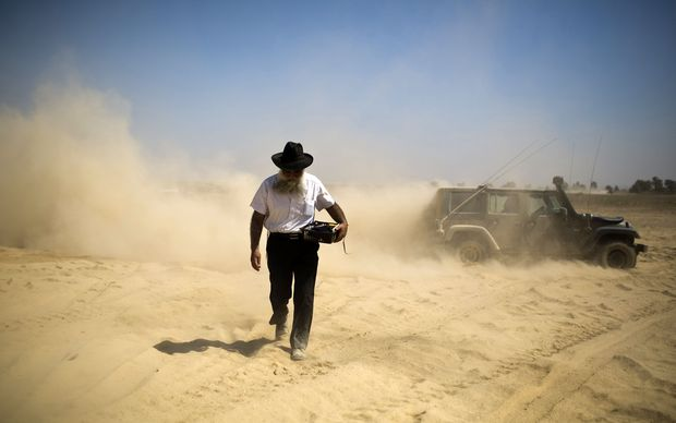 An ultra-Orthodox Jewish man carries prayer paraphernalia at a staging area outside the Gaza Strip.
