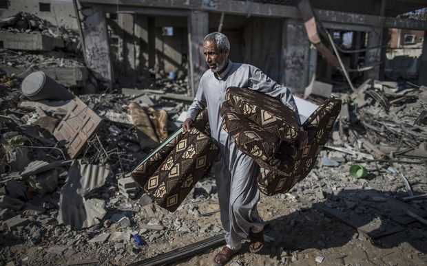 A Palestinian salvages cushions found in the rubble of destroyed buildings  in the Shejaiya residential district of Gaza City.