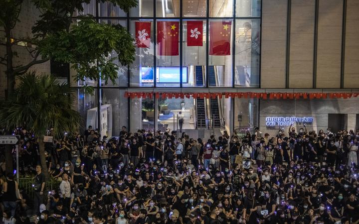 Protester are seen holding up purple lights while standing in front of China and Hong Kong Flags during a rally in Hong Kong on August 28, 2019.