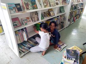 Local children shelving books in Tonga's first public library