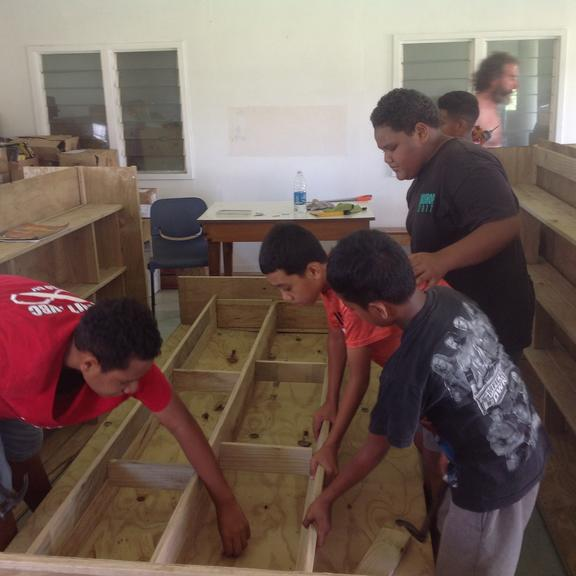 Children in Tonga put together shelves for Tonga's first public library