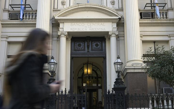 A woman passes by the headquarters of Argentina's Central Bank in the financial district of Buenos Aires