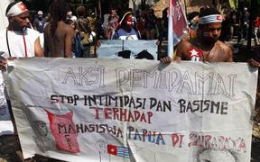 Papuan demonstrators holding a banner that says 'stop intimidation and racism towards students of Papua'.