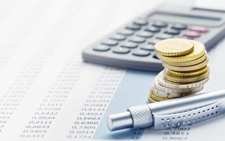 Finance - coins, calculator and table of figures.