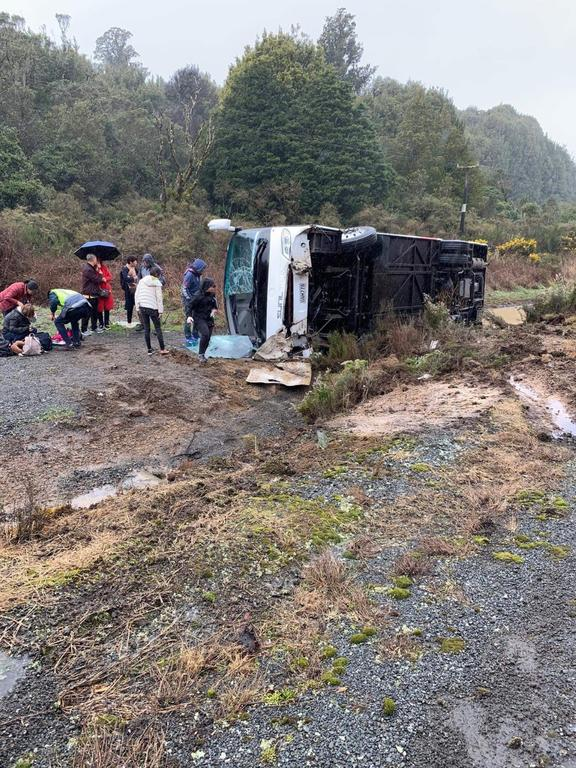 People support one another at the bus crash near Rotorua that has killed at least five people.