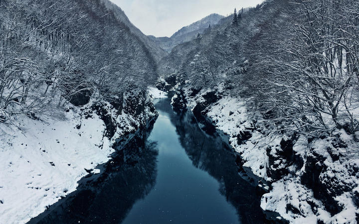 The Tone River with snowy banks in winter. Minakami, Japan