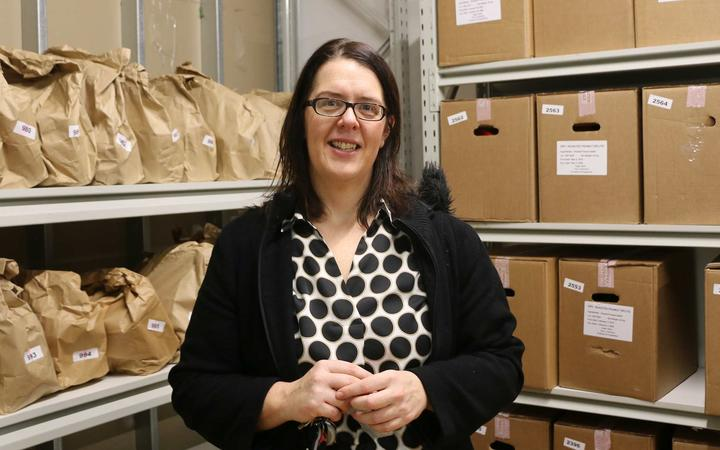 Woman stands in front of shelves with boxes and paper bags filled with food.