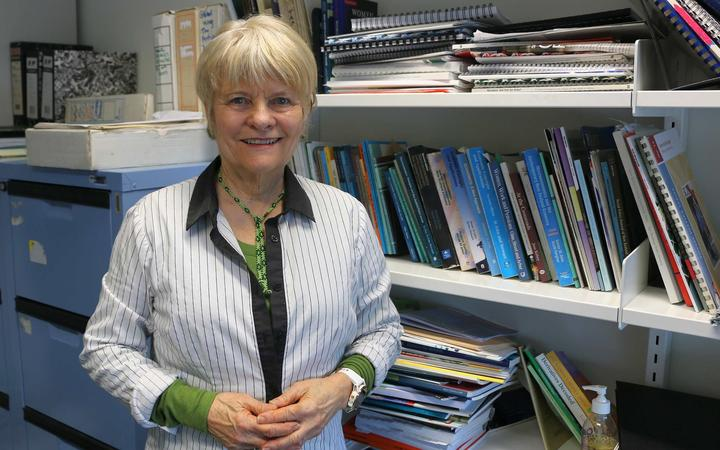 Woman stands in front of  work bookshelf