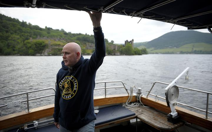 Professor Neil Gemmell on his boat as he conducts research into the DNA present in the waters of Loch Ness in the Scottish Highlands Scotland