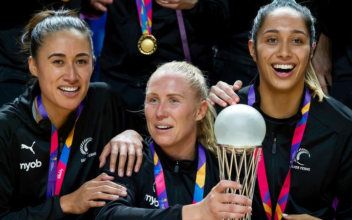 New Zealand captain Laura Langman holds the Netball World Cup trophy along with Maria Folau and Phoenix Karaka.