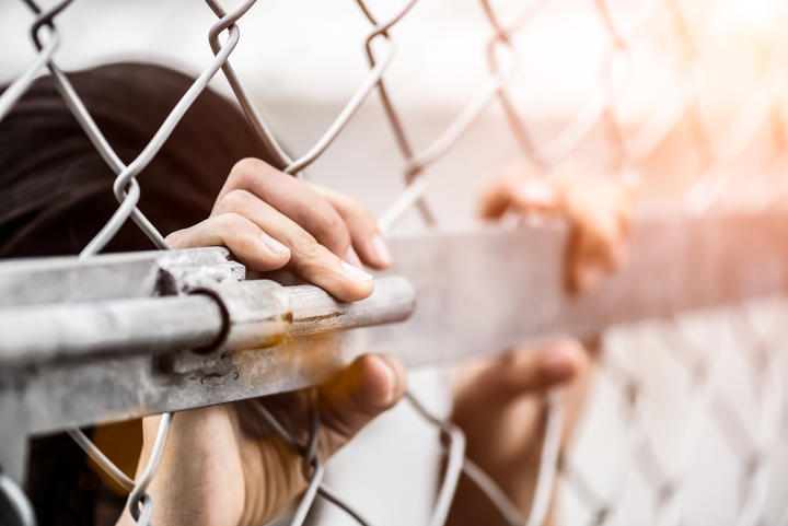 Woman hand holding on chain link fence for remember Human Rights Day concept.