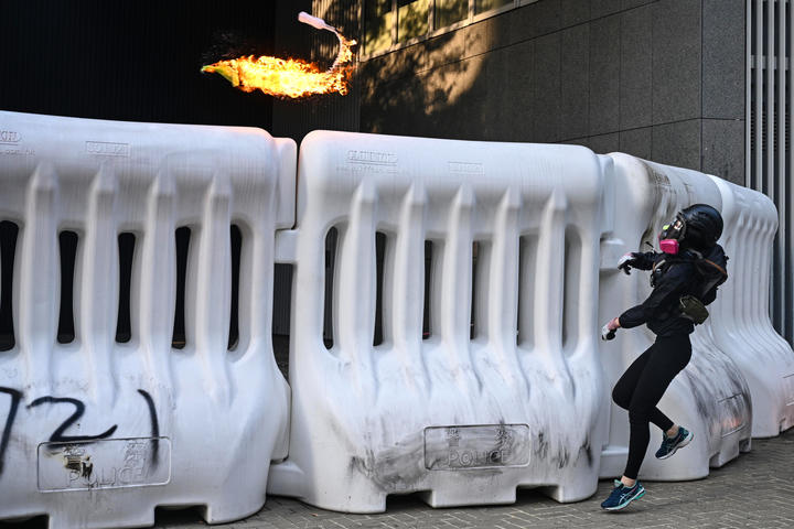 A protester throws a molotov cocktail over a barricade outside the government headquarters in Hong Kong on September 15, 2019.