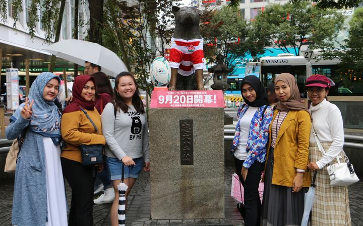 Tourists pose with the Hachiko statue in Tokyo.