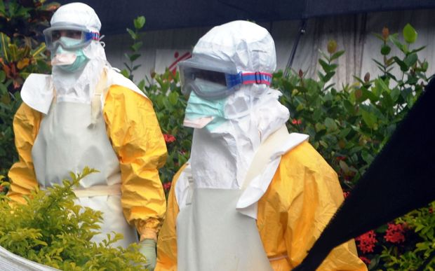 Members of Doctors Without Borders (MSF) wearing protective gear outside an Ebola isolation ward in Guinea