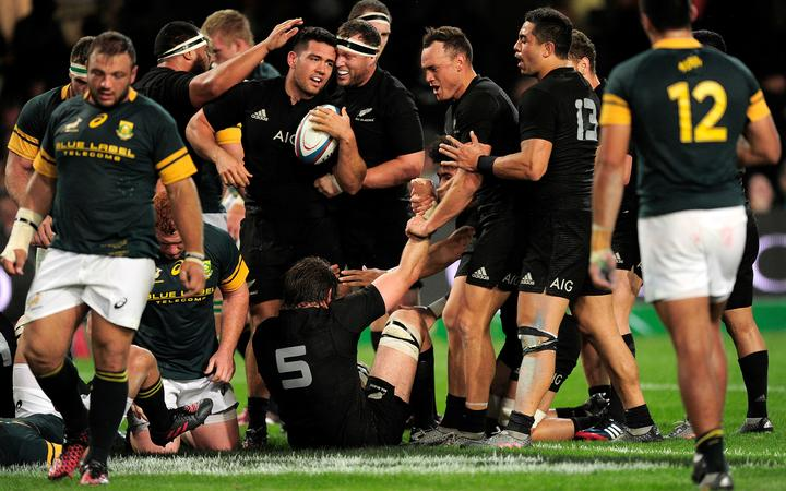 Codie Taylor is congratulated by his All Blacks team mates after scoring against Springboks in Durban 2016.