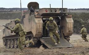 Australian Army soldiers run from an armoured personnel carrier during Excercise Chong Ju, a live fire demonstration showcasing the army's joint combined arms capabilities at the Puckapunyal Military Base north of Melbourne on May 9, 2019.