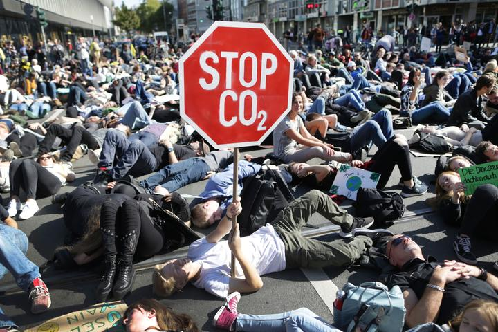 """20 September 2019, North Rhine-Westphalia, Duesseldorf: Participants in a demonstration lie at a crossroads. A demonstrator holds up his poster """"Stop CO2""""."""