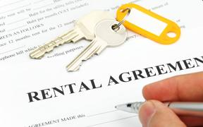14588891 - rental agreement form with signing hand and keys and pen