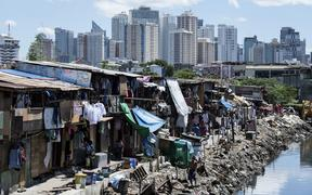 People living in a settlement walk about, as the skyline of Manila's financial district is seen in the background, on August 17, 2017.