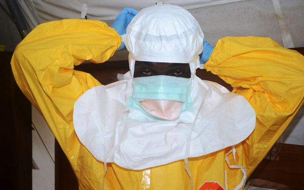 A member of Doctors Without Borders puts on protective gear in an isolation ward.