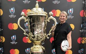 Kate Lawless posing with an enlarged replica of the Webb Ellis trophy.