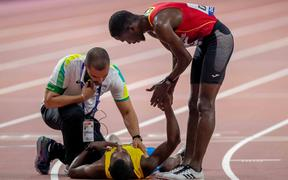 Braima Suncar Dabo of Guinea-Bissau checks on Aruba's Jonathan Busby after he helped him up the finishing straight of the men's 5000m.