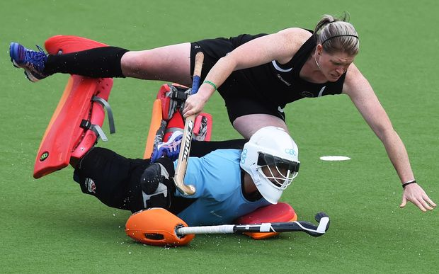 Katie Glynn trips over England Goalie Maddie Hinch during the Black Sticks' loss in the Glasgow semi-final.