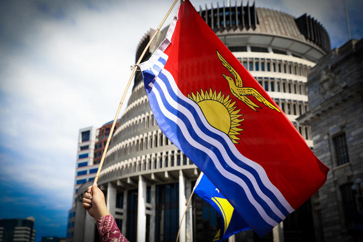 The Kiribati flag is waved in front of the Beehive in Wellington.