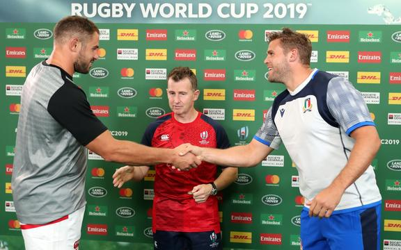Captains Tyler Ardron (Canada) and Dean Budd (Italy) at the coin toss as referee Nigel Owens looks on.