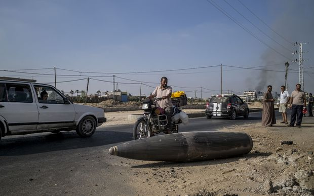 Palestinian onlookers pause to inspect an Israeli army bomb laying unexploded on the road that links northern and southern Gaza.