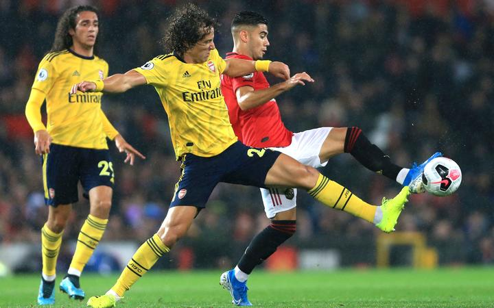 David Luiz of Arsenal challenges Andreas Pereira of Manchester United for the ball.