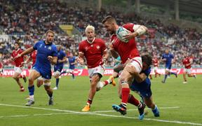 DTH Van Der Merwe screams to team-mate Patrick Parfrey to off load as he is tackled by Italy's Matteo Minozzi.