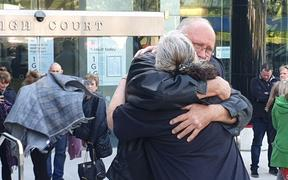 Lois Tolley's family embrace outside court today.