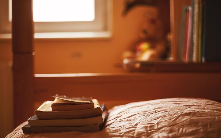 Some books on the bed in the calm ambiance of teenager's room.