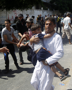 Injured people are carried from the scene of an Israeli strike on a UN school in Rafah.
