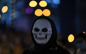 A protester looks on while wearing a mask at Admiralty area in Hong Kong on late October 4, 2019, as people hit the streets after the government announced a ban on facemasks.
