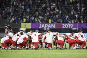 Tonga's players pray after their dramatic defeat by France.