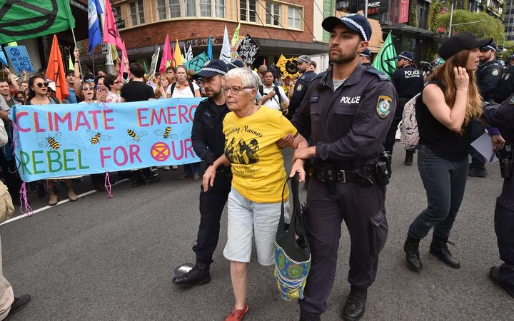 An Extinction Rebellion activist (C) is arrested by police after hundreds of protesters staged a sit-in on a busy inner-city road in Sydney on October 7, 2019.