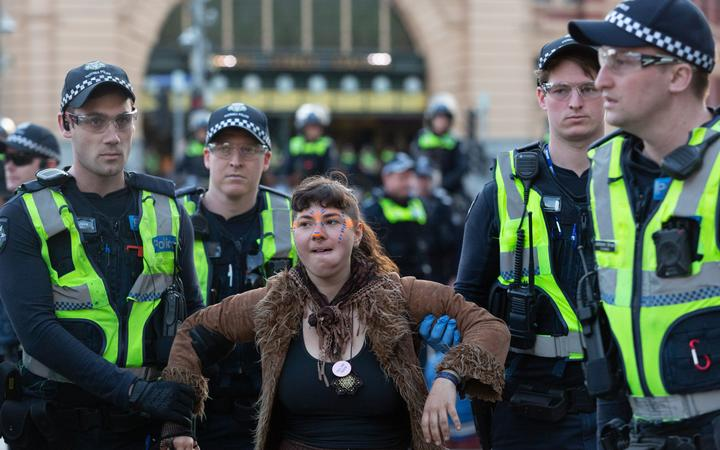 A demonstrator is arrested by police during a Extinction Rebellion protest in Melbourne on October 7, 2019.