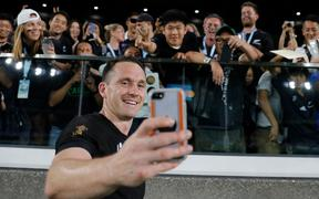 All Blacks full back Ben Smith takes a selfie with fans after winning the Japan 2019 Rugby World Cup Pool B match between New Zealand and South Africa.